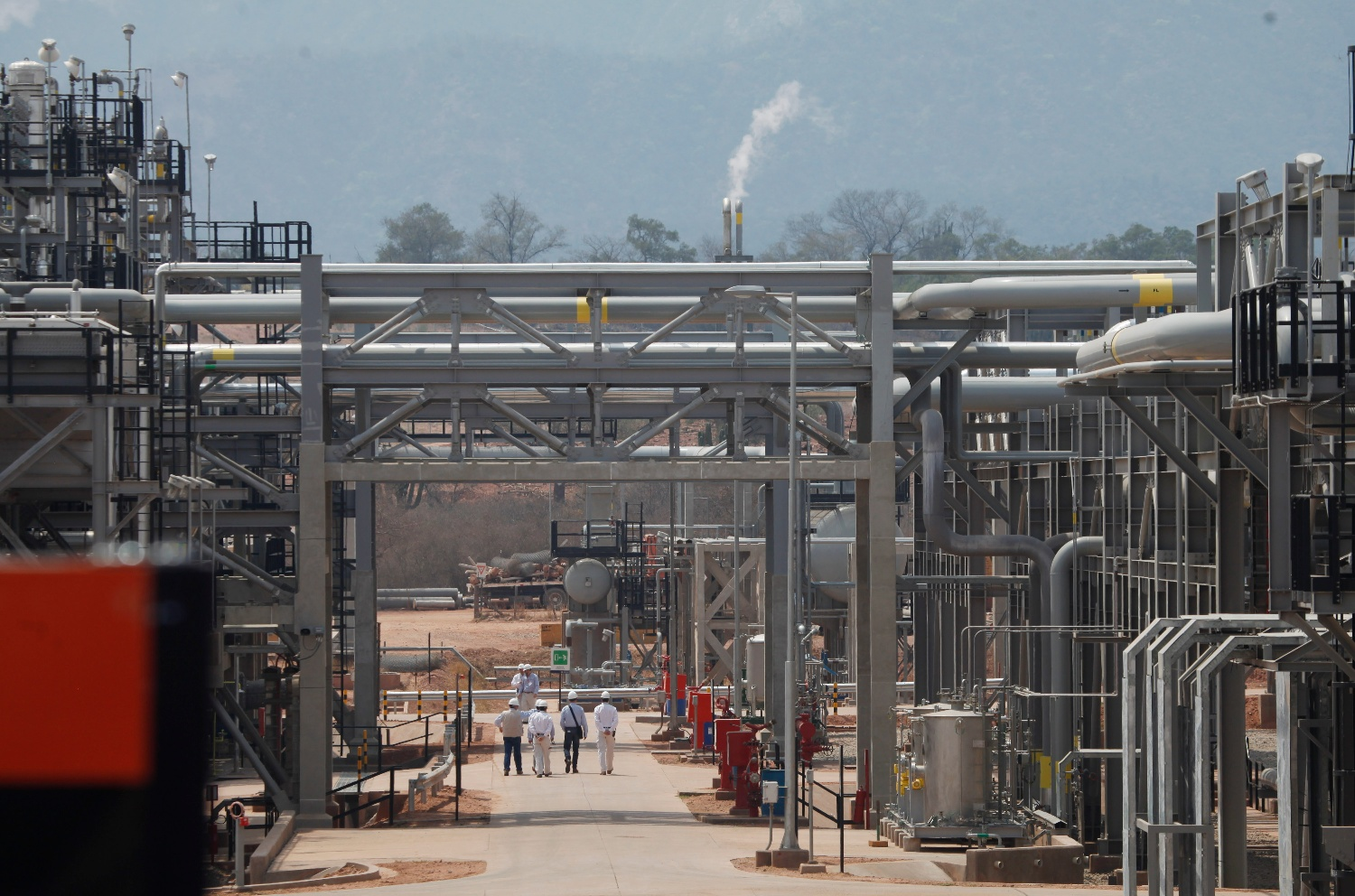 A group walks through an area at the Repsol plant before a ceremony to inaugurate the completion of a new phase at the Margarita-Huacaya gas refinery in the region of Chaco, southeast of Bolivia, Tuesday, Oct. 1, 2013.